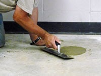 Repairing the cored holes in the concrete slab floor with fresh concrete and cleaning up the Fayetteville home.
