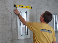 Positioning a wall plate cover on a foundation wall in Philpot.